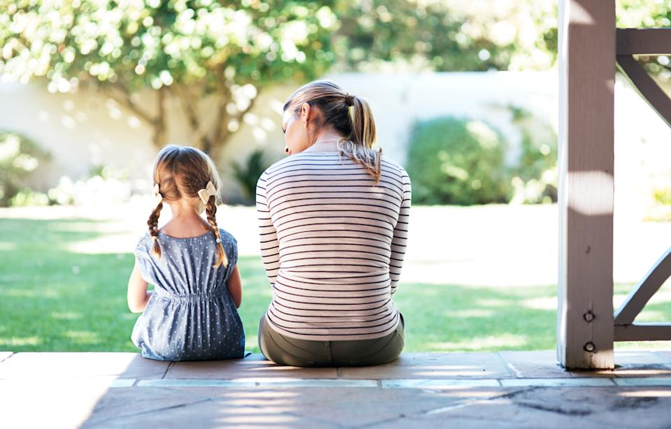 Rearview shot of a young woman and her daughter having a conversation on the porch