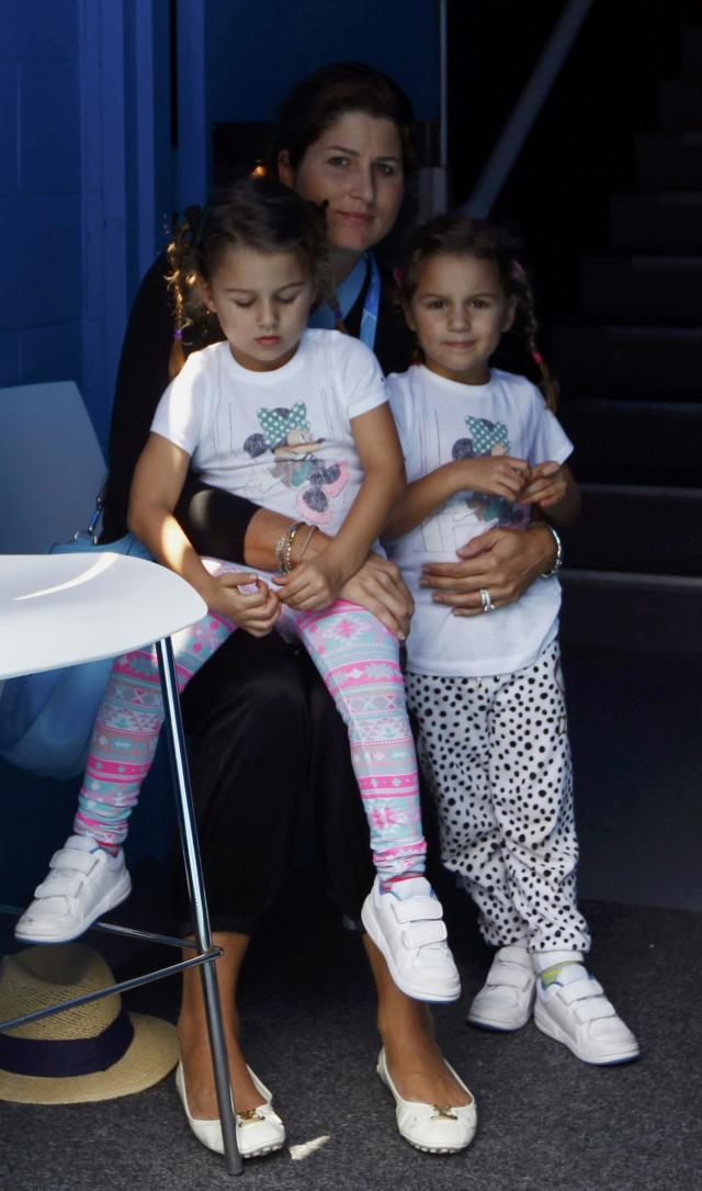 Mirka Federer (R), wife of Roger Federer of Switzerland, sits with their twin girls Myla Rose and Charlene Riva as they watch Federer arrive on court for his men's singles match against Teymuraz Gabashvili of Russia at the Australian Open 2014 tennis tournament in Melbourne January 18, 2014. REUTERS/David Gray (AUSTRALIA - Tags: SPORT TENNIS ENTERTAINMENT)