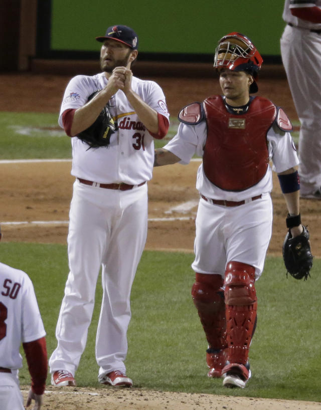 St. Louis Cardinals catcher Yadier Molina talks with starting pitcher Lance Lynn after walking Boston Red Sox's Xander Bogaerts during the fifth inning of Game 4 of baseball's World Series Sunday, Oct. 27, 2013, in St. Louis. (AP Photo/Charlie Riedel)