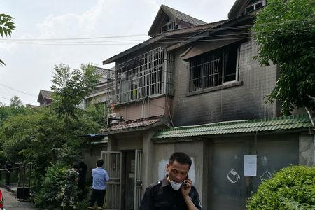 People are seen outside a residential building where a fire that broke out in the early morning killed and injured many residents, in Changshu