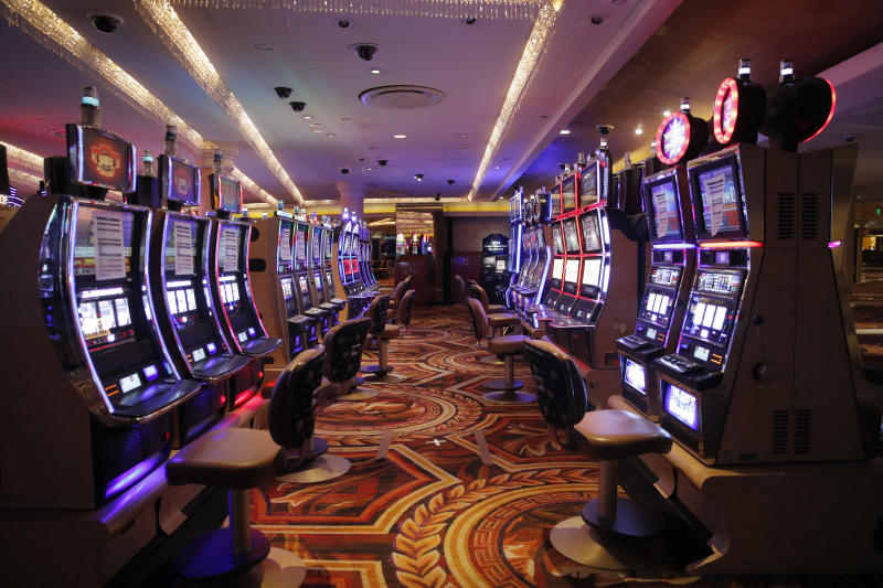 Chairs have been removed at some electronic slot machines to maintain social distancing between players at a closed Caesars Palace hotel and casino Thursday, May 21, 2020, in Las Vegas. Casino operators in Las Vegas are awaiting word when they will be able to reopen after a shutdown during the coronavirus outbreak. (AP Photo/John Locher)