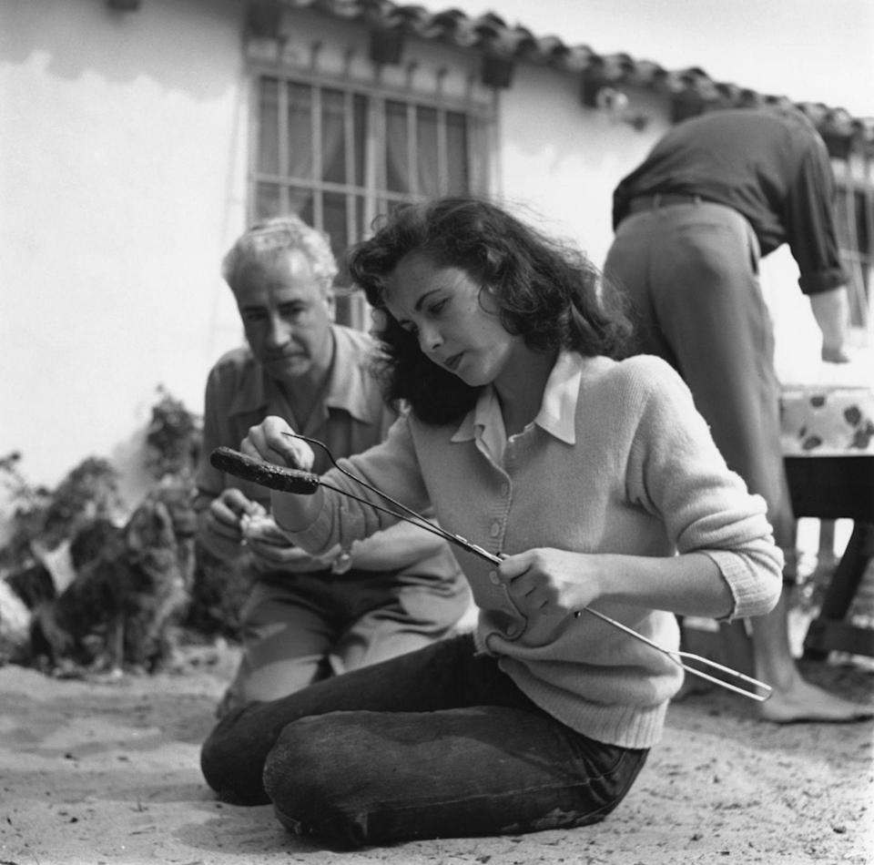 <p>Elizabeth inspects a hot dog she's roasting while at a BBQ. For the event, the actress ditched her normal glam and instead opted for jeans and a cardigan. </p>