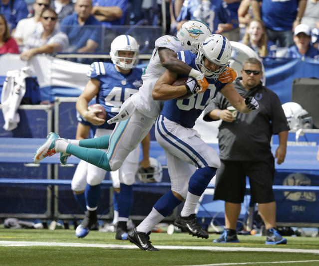 Indianapolis Colts' Coby Fleener (80) is tackled by Miami Dolphins' Reshad Jones (20) during the first half an NFL football game Sunday, Sept. 15, 2013, in Indianapolis. (AP Photo/Michael Conroy)