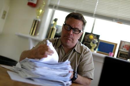 FILE PHOTO: Scott Rosmarin, owner and operator of Rosmarins Day Camp and Cottages, sorts campers' immunization forms at the camp office in Monroe, New York, U.S., May 20, 2019. Picture taken May 20, 2019. REUTERS/Mike Segar