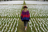 "Artist Suzanne Brennan Firstenberg walks among thousands of white flags planted in remembrance of Americans who have died of COVID-19, Tuesday, Oct. 27, 2020, near Robert F. Kennedy Memorial Stadium in Washington. Firstenberg's temporary art installation, called ""In America, How Could This Happen,"" will include an estimated 240,000 flags when completed. (AP Photo/Patrick Semansky)"