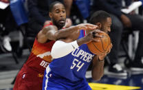 Denver Nuggets forward Will Barton, left, tries to steal the ball from Los Angeles Clippers forward Patrick Patterson during the first half of an NBA basketball game Friday, Dec. 25, 2020, in Denver. (AP Photo/David Zalubowski)