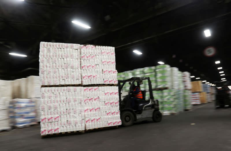 FILE PHOTO: An employee operates a forklift to move pallets of toilet paper at a warehouse of the Syassky Pulp & Paper Mill in Syasstroy