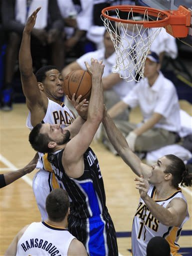 Orlando Magic's Ryan Anderson, middle, puts up a shot against Indiana Pacers' Danny Granger, left, and Lou Amundson during the first half of an NBA first-round playoff basketball game Monday, April 30, 2012, in Indianapolis. (AP Photo/Darron Cummings)