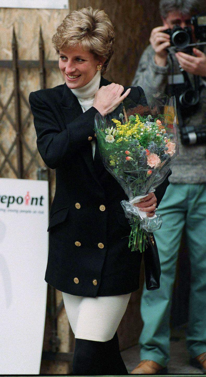 <p>Diana paired a black blazer with gold buttons over a cream turtleneck for a visit to Centrepoint in January 1995.<br></p>