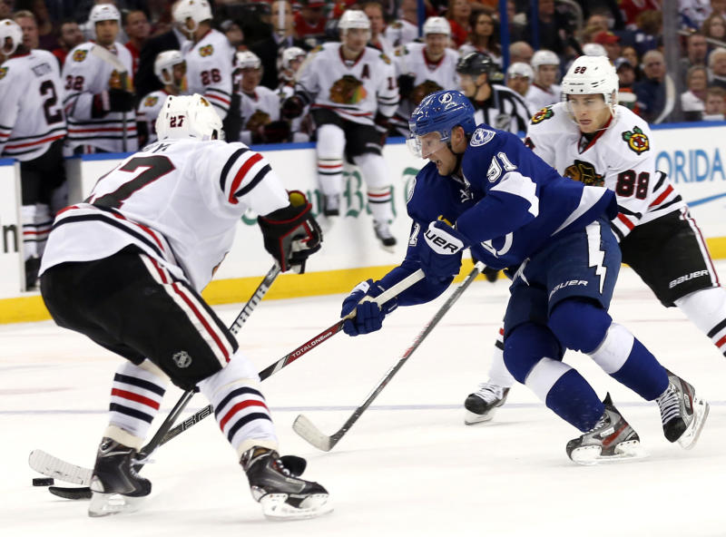 Tampa Bay Lightning center Steven Stamkos (91), of Canada, threads between Chicago Blackhawks defenseman Johnny Oduya (27), of Sweden, and Patrick Kane (88) to score during the second period of an NHL hockey game on Thursday, Oct. 24, 2013, in Tampa, Fla. (AP Photo/Reinhold Matay)