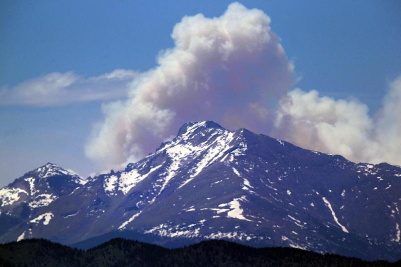 A plume of smoke from the Big Meadows Fire in Rocky Mountain National Park rises above Longs Peak, as seen from just east of Boulder, Colo., Tuesday June 11, 2013. A National Park crew has assessed the fire that has been confirmed on the north end of Big Meadows on the west side of the park. (AP Photo/Brennan Linsley)