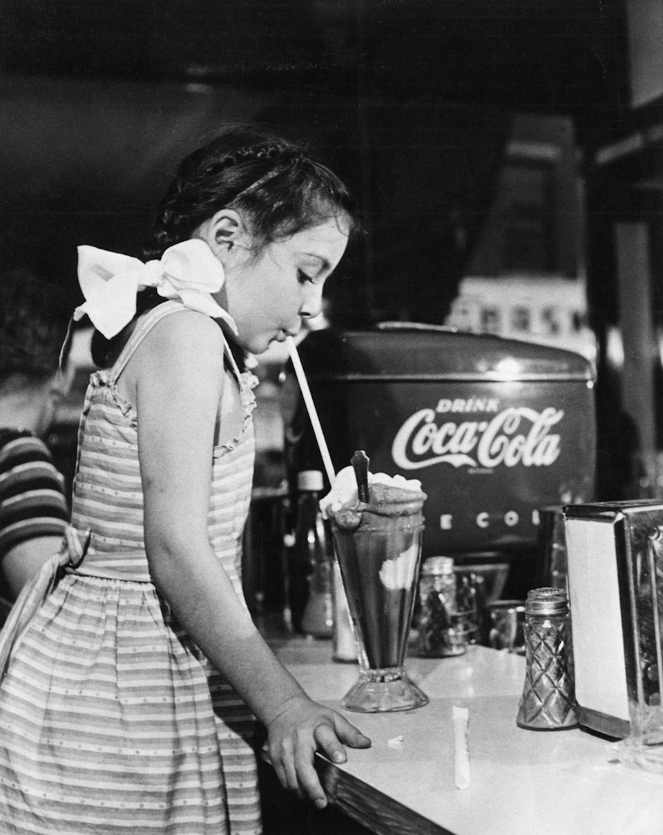 """<p>A little girl sips down a chocolate milkshake at an ice cream parlor located in the back of a drugstore—<a href=""""https://www.drugstoremuseum.com/soda-fountain/soda-fountain-history/"""" rel=""""nofollow noopener"""" target=""""_blank"""" data-ylk=""""slk:a common location"""" class=""""link rapid-noclick-resp"""">a common location</a> for many parlors in the early to mid-1900s.</p>"""