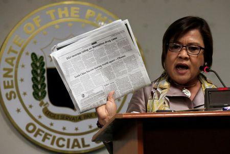 Former Justice Secretary and current Senator Leila De Lima shows reporters an article published on a local newspaper during a news conference at the Senate headquarters in Pasay city, metro Manila, Philippines September 22, 2016. REUTERS/Romeo Ranoco