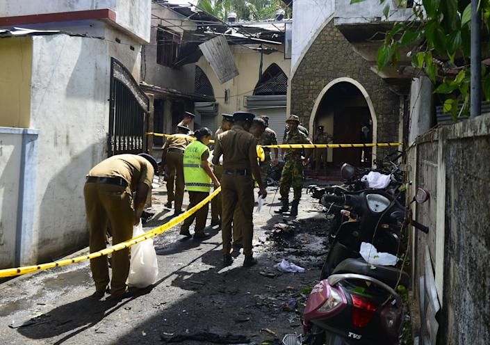 Sri Lankan security personnel and investigators look through debris outside Zion Church following an explosion in Batticaloa in eastern Sri Lanka.