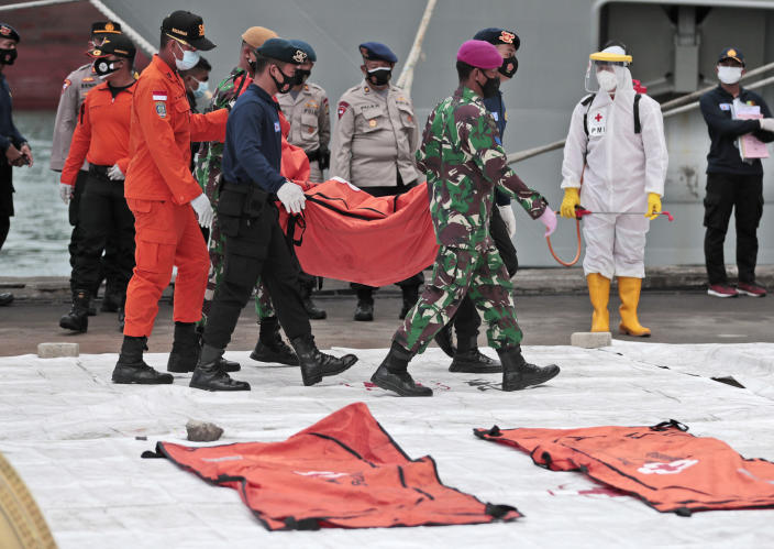 Rescuers carry a body bag of items recovered from the Sriwijaya Air passenger jet crash at Tanjung Priok Port, Tuesday, Jan. 12, 2021. Indonesian navy divers were searching through plane debris and seabed mud Tuesday looking for the black boxes of a Sriwijaya Air jet that nosedived into the Java Sea over the weekend with 62 people aboard. (AP Photo/Dita Alangkara)
