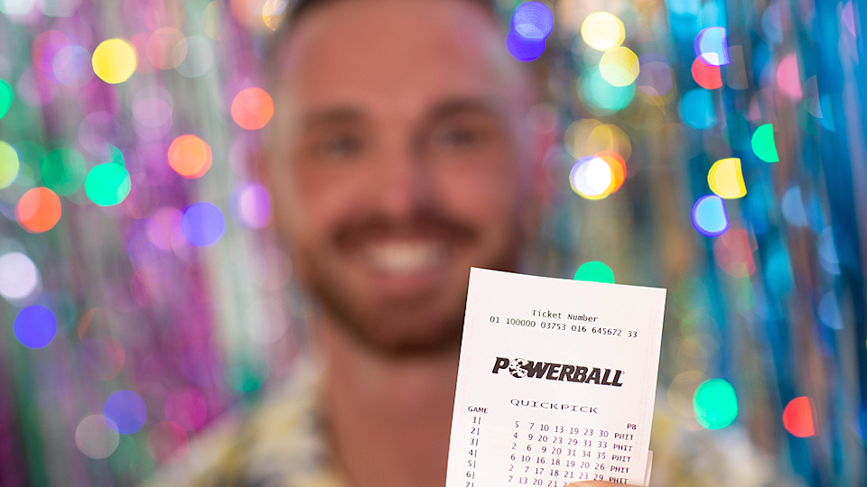 A man is pictured holding a Powerball ticket.