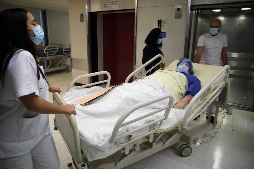 Caroline Erganian, a retired secretary, is moved on a gurney for her surgery at Bichat Hospital, AP-HP, in Paris, Wednesday, Dec. 2, 2020. (AP Photo/Francois Mori)