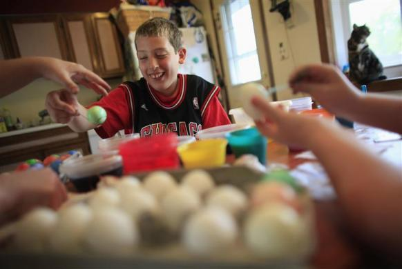 Parker Roos, who suffers from Fragile X, shares a laugh with his mother Holly and his sister Allison as they dye Easter eggs at their home in Canton, Illinois, April 4, 2012.