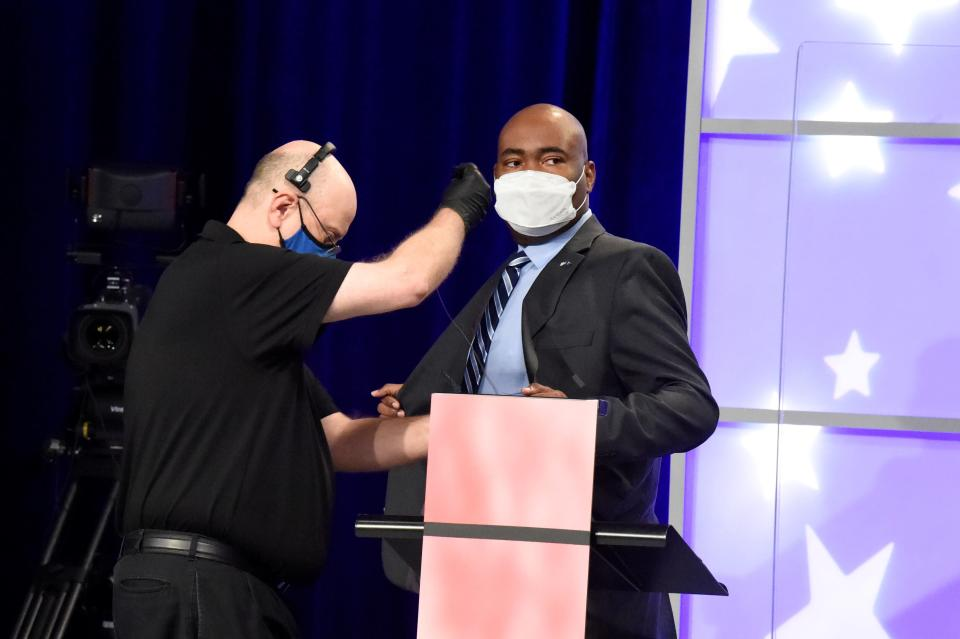 Democratic challenger Jaime Harrison, right, is fitted for a microphone before a debate with U.S. Sen. Lindsey Graham of South Carolina on Friday, Oct. 30, 2020, in Columbia, S.C. (AP Photo/Meg Kinnard)