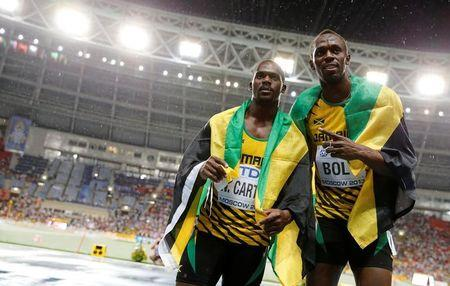 First placed Bolt of Jamaica poses with his compatriot third placed Carter after competing in the men's 100 metres final during the IAAF World Athletics Championships at the Luzhniki stadium in Moscow