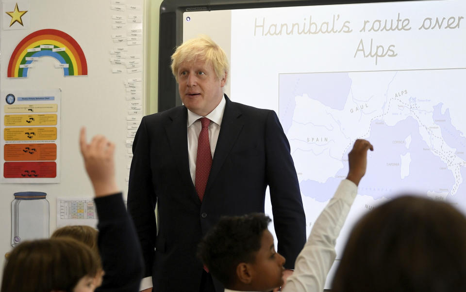 Britain's Prime Minister Boris Johnson, left, visits Pimlico Primary school in London, Tuesday July 10, 2018, to meet staff and students. (Toby Melville/Pool via AP)