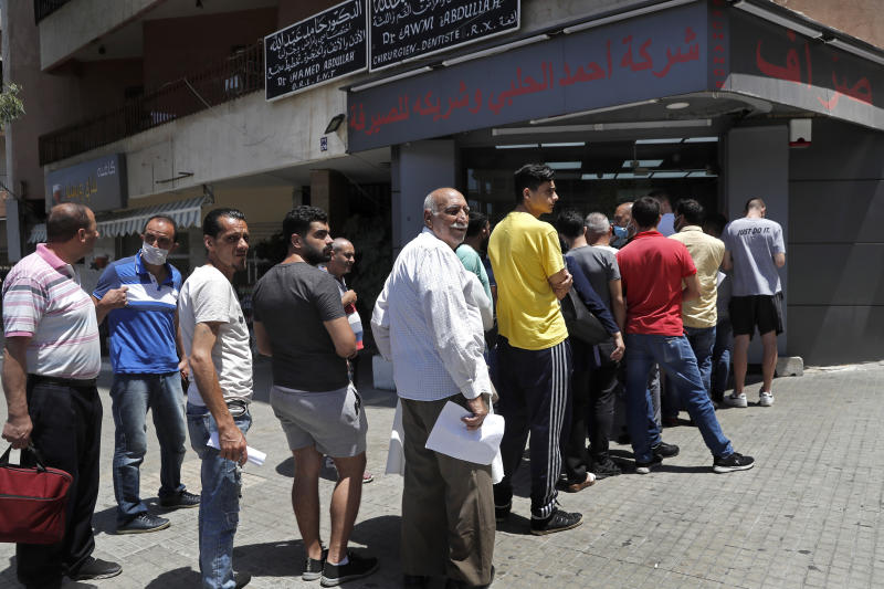 People line up outside an exchange shop to buy U.S. dollars, in Beirut, Lebanon, June 17, 2020. Lebanon's financial meltdown has thrown its people into a frantic search for dollars as the local currency's value evaporates. Long, raucous lines mass outside exchange bureaus to buy rationed dollars. Many try to rescue their dollars trapped in bank accounts frozen by the government. With tens of thousands thrown into poverty, the turmoil is fueling bitterness at banks and politicians.(AP Photo/Hussein Malla)