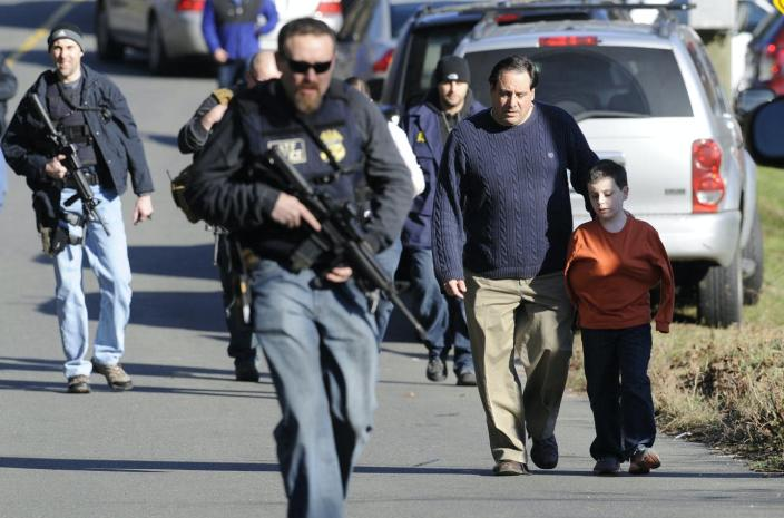 A parent with a child walks near police officers with rifles.