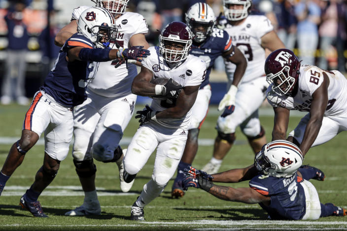Texas A&M running back Devon Achane (6) carries the ball as Auburn defensive back Jaylin Simpson (36) and linebacker Zakoby McClain (9) try and stop him during the second half of an NCAA college football game on Saturday, Dec. 5, 2020, in Auburn, Ala. (AP Photo/Butch Dill)
