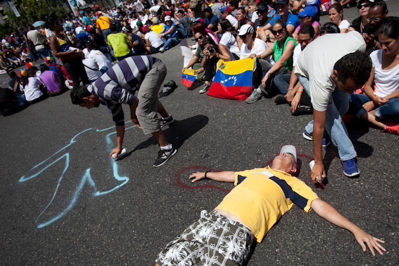Demonstrators paint their silhouettes during a protest asking for the disarmament of armed groups in Caracas, Venezuela, Sunday, Feb. 16, 2014. For the past several days, protests have rocked Caracas yielding several dead and scores of wounded in clashes between opposition protesters with security forces and pro-government supporters. (AP Photo/Alejandro Cegarra)