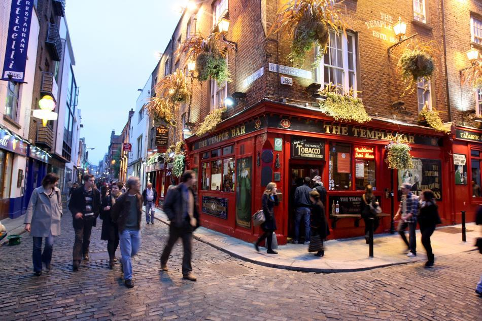 People walk past the Temple Bar pub in Temple Bar in Dublin, Ireland.
