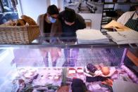 People view food items for sale inside 'Rudy's Vegan Butcher' shop, amid the coronavirus (COVID-19) outbreak, in London
