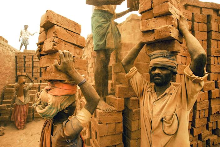 Migrant workers pile 20 bricks at a time on top of their heads, as dust falls in their faces
