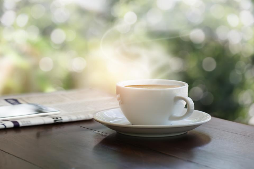 A cup of coffee on teak wood table with blurred mobile phone on newspaper, garden bokeh background.