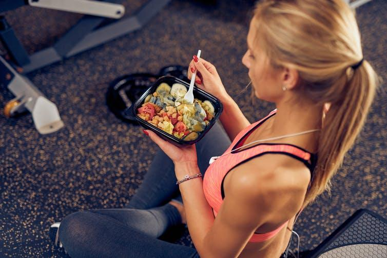 Woman sitting on the floor of the gym eating a healthy meal.