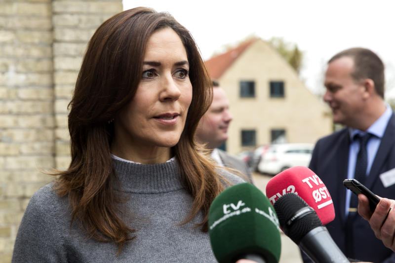 A photo of Princess Mary wearing a grey jumper and speaking into a microphone.