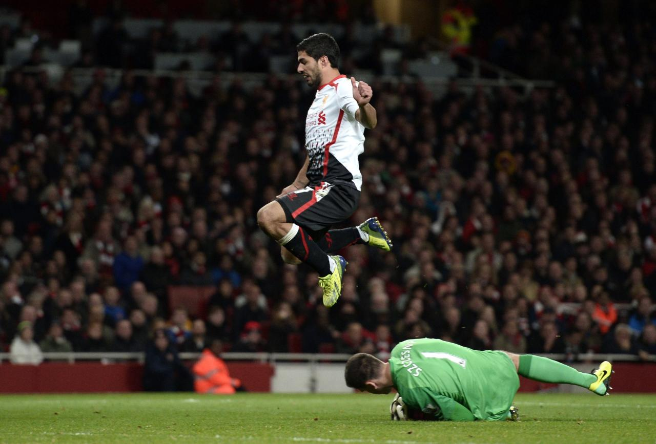 """Liverpool's Luis Suarez jumps over Arsenal's goalkeeper Wojciech Szczesny during their English Premier League soccer match at the Emirates stadium in London November 2, 2013. REUTERS/Dylan Martinez (BRITAIN - Tags: SPORT SOCCER) FOR EDITORIAL USE ONLY. NOT FOR SALE FOR MARKETING OR ADVERTISING CAMPAIGNS. NO USE WITH UNAUTHORIZED AUDIO, VIDEO, DATA, FIXTURE LISTS, CLUB/LEAGUE LOGOS OR """"LIVE"""" SERVICES. ONLINE IN-MATCH USE LIMITED TO 45 IMAGES, NO VIDEO EMULATION. NO USE IN BETTING, GAMES OR SINGLE CLUB/LEAGUE/PLAYER PUBLICATIONS"""