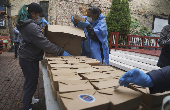 Volunteers unload boxed meals prepared at the South Bronx restaurant La Morada, Oct. 28, 2020, in New York. After a fund raising campaign during the coronavirus pandemic, La Morada, an award winning Mexican restaurant, was reopened and now also functions as a soup kitchen, serving 650 meals daily. (Bebeto Matthews / AP)