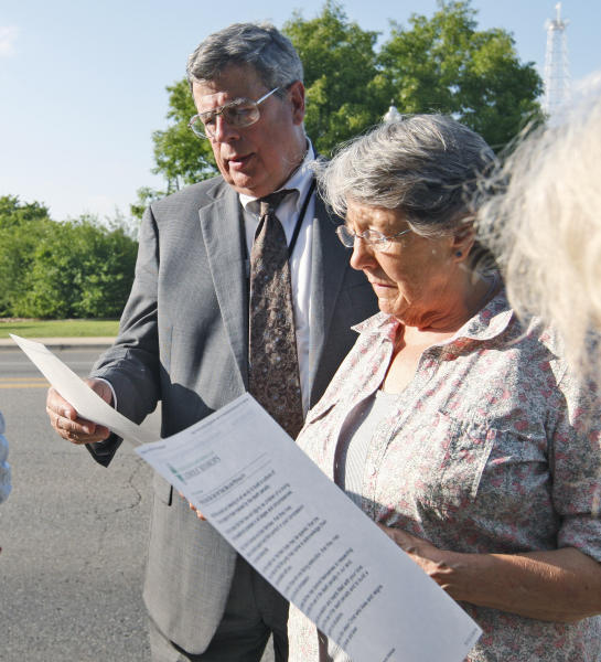 Death penalty opponents Jim Rowan left, and Margaret Cox, right, read a prayer as part of a protest in Oklahoma City, Tuesday, May 1, 2012, for the execution of Michael Bascum Selsor. An Oklahoma man convicted of murdering a Tulsa convenience store manager almost 37 years ago was executed by lethal injection Tuesday. (AP Photo/Sue Ogrocki)