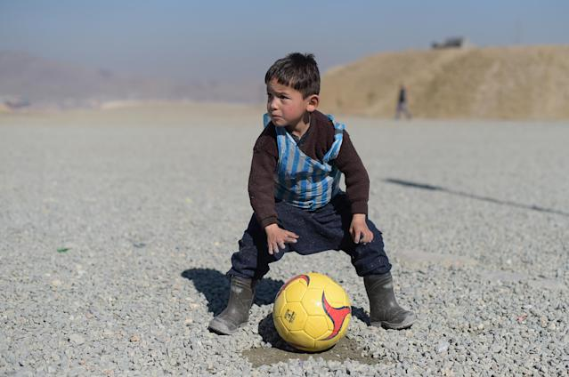 <p>Afghan boy five-year-old Murtaza Ahmadi, a young Lionel Messi fan, plays football in Kabul on February 1, 2016. Barcelona star Lionel Messi is hoping to arrange a meeting with an Afghan boy who shot to fame after pictures of him dressed in a striped plastic bag jersey went viral, Kabul's football federation said on February 1. (Photo: Shah Marai/ AFP/Getty Images) </p>