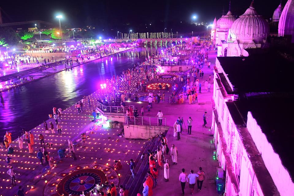 Hindu devotees gather whiel lighting earthen lamps on the banks of the River Sarayu on the eve before the groundbreaking ceremony of the proposed Ram Temple in Ayodhya on August 4, 2020. - India's Prime Minister Narendra Modi will lay the foundation stone for a grand Hindu temple in a highly anticipated ceremony at a holy site that was bitterly contested by Muslims, officials said. The Supreme Court ruled in November 2019 that a temple could be built in Ayodhya, where Hindu zealots demolished a 460-year-old mosque in 1992. (Photo by SANJAY KANOJIA / AFP) (Photo by SANJAY KANOJIA/AFP via Getty Images)