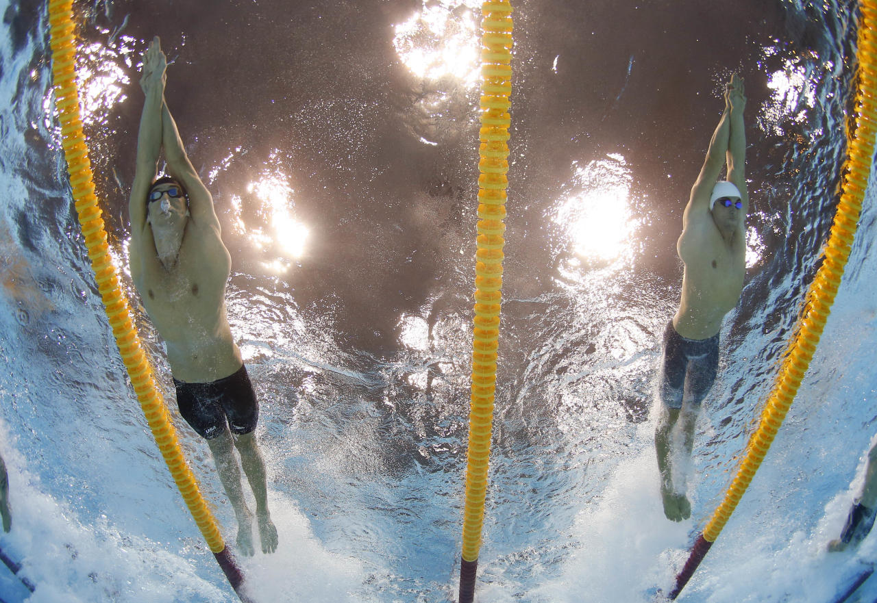 United States' Michael Phelps, left, and France's Fabien Gilot compete in the men's 4x100-meter freestyle relay final at the Aquatics Centre in the Olympic Park during the 2012 Summer Olympics in London, Sunday, July 29, 2012. (AP Photo/David J. Phillip)