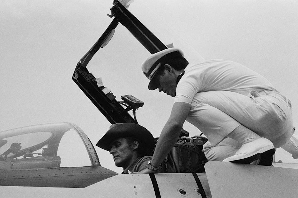 <p>Dennis Hopper jumps into the cockpit and gets a look behind the wheel of an aircraft carrier battleship in 1976. </p>