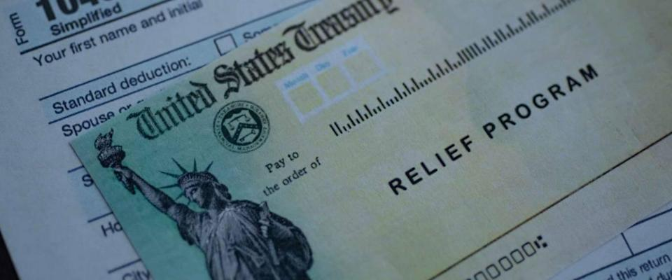 Form 1040 U.S. Individual Income tax return next to the Stimulus Check Relief program. Close up view.