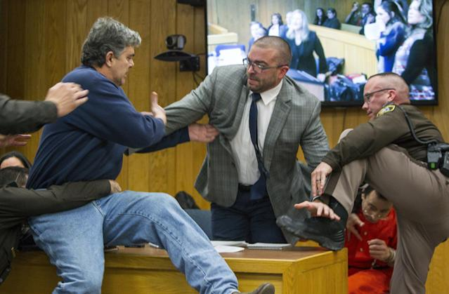 Randall Margraves, left, lunges at Larry Nassar, bottom right, in a Michigan court room. (AP)