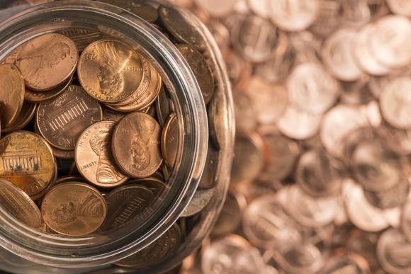 Jar of pennies with more pennies surrounding it.