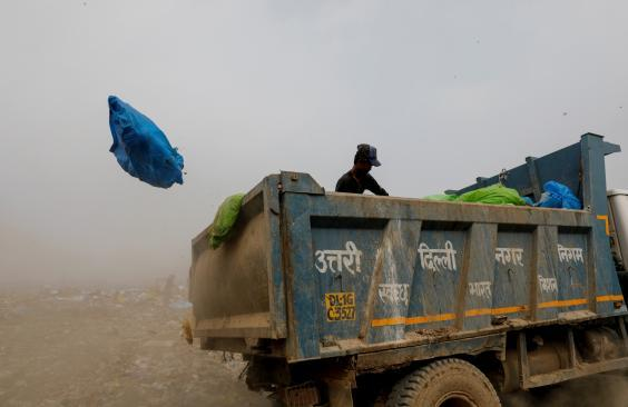 A waste collector goes through bags of rubbish as he throws them off the truck (Reuters)
