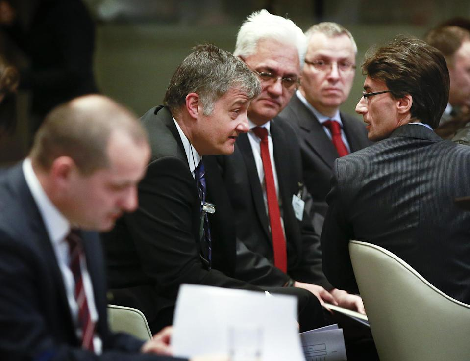 Members of the Serbian delegation Petar Vico, second left and Sasa Obradovic, right, and Croatian Minister Orsat Miljenic, left, await the start of public hearings at the International Court of Justice (ICJ) in The Hague, Netherlands, Monday, March 3, 2014. Croatia is accusing Serbia of genocide during fighting in the early 1990's as the former Yugoslavia shattered in spasms of ethnic violence, in a case at the United Nations' highest court that highlights lingering animosity in the region. Croatia is asking the ICJ to declare that Serbia breached the 1948 Genocide Convention when forces from the former Federal Republic of Yugoslavia attempted to drive Croats out of large swaths of the country after Zagreb declared independence in 1991. (AP Photo/Jiri Buller)