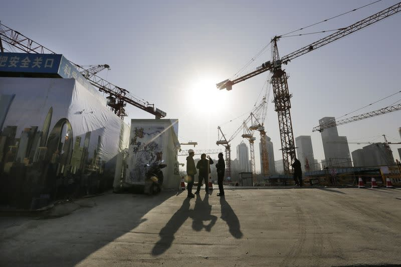 Workers chat outside a construction site in Beijing's central business district
