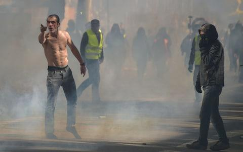 """""""Yellow vests"""" protesters stand amid tear gas smokes as during a demonstration - Credit: PASCAL PAVANI/AFP"""