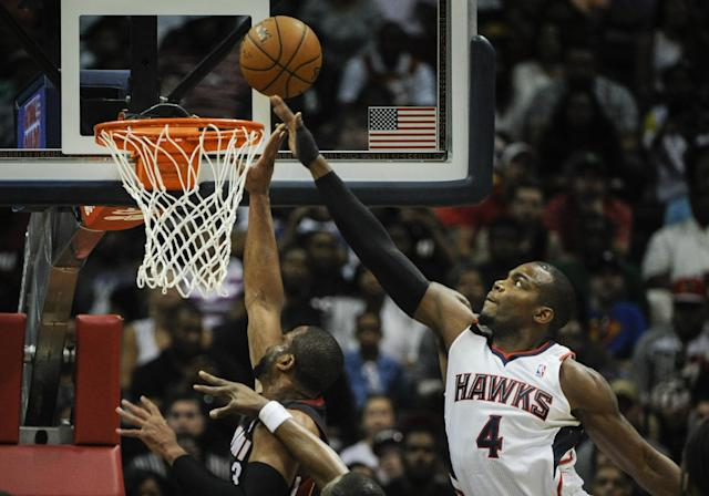 Atlanta Hawks forward Paul Millsap (4) gets his hand on a shot by Miami Heat guard Dwyane Wade (3) during the first half of an NBA basketball game on Saturday, April 12, 2014, in Atlanta. (AP Photo/John Amis)